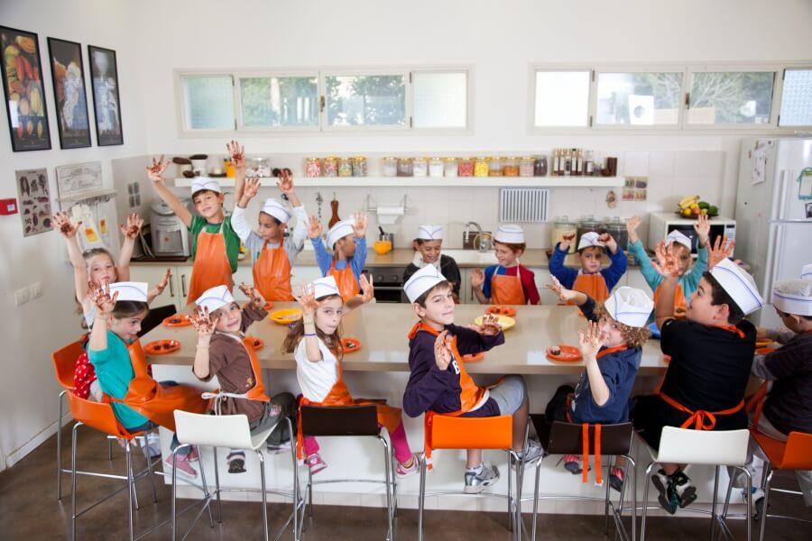 ילדים מנופפים למצלמה בסדנת שוקולד